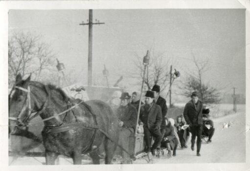 Fotografia kuligu kilka osób siedzących w powozie ciągnięty przez konie na ulicy w śnieżnej scenerii
