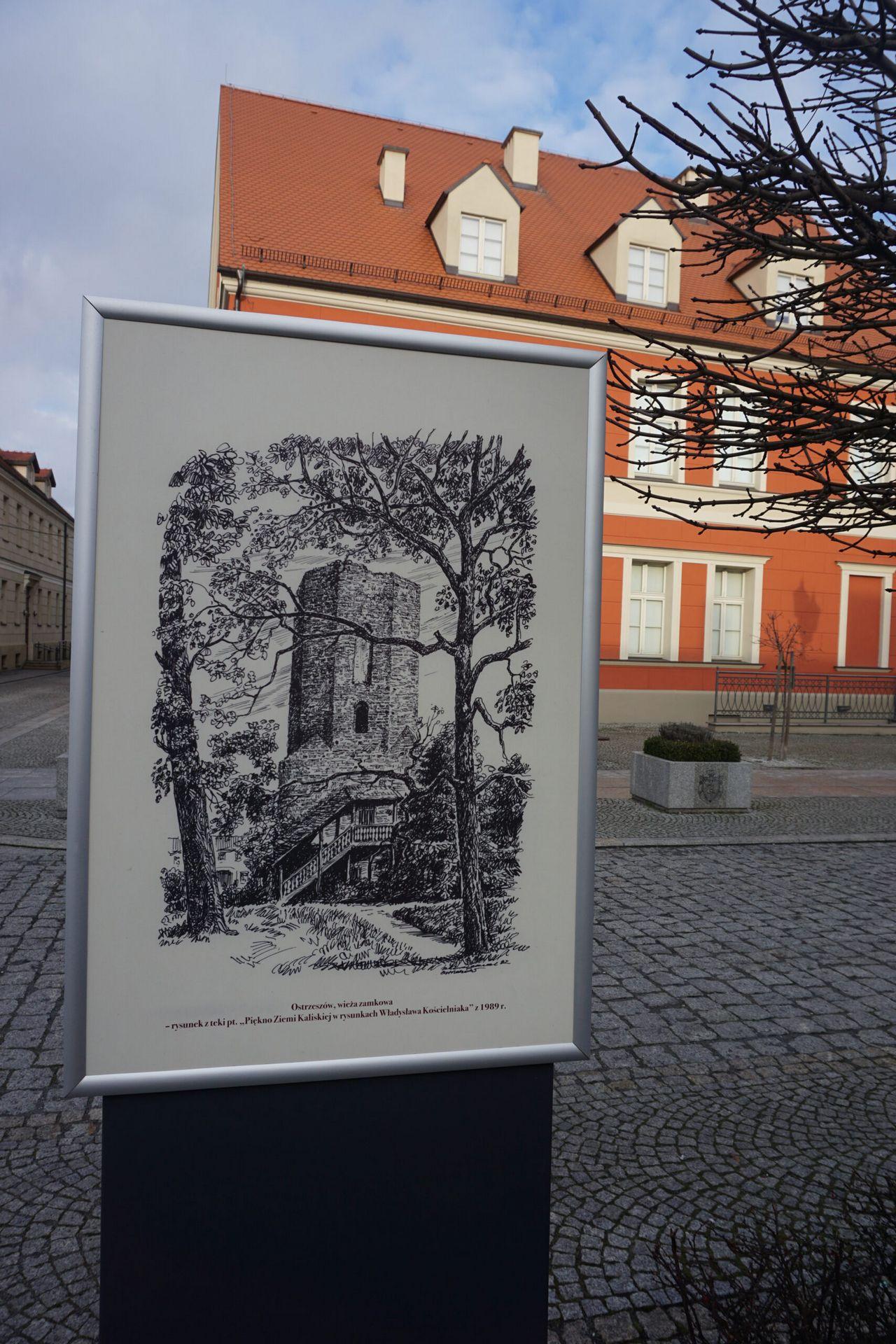 Zdjęcie gabloty z planszą na której znajduje się rysunek Władysława Kościelniaka wieża zamkowa w Ostrzeszowie