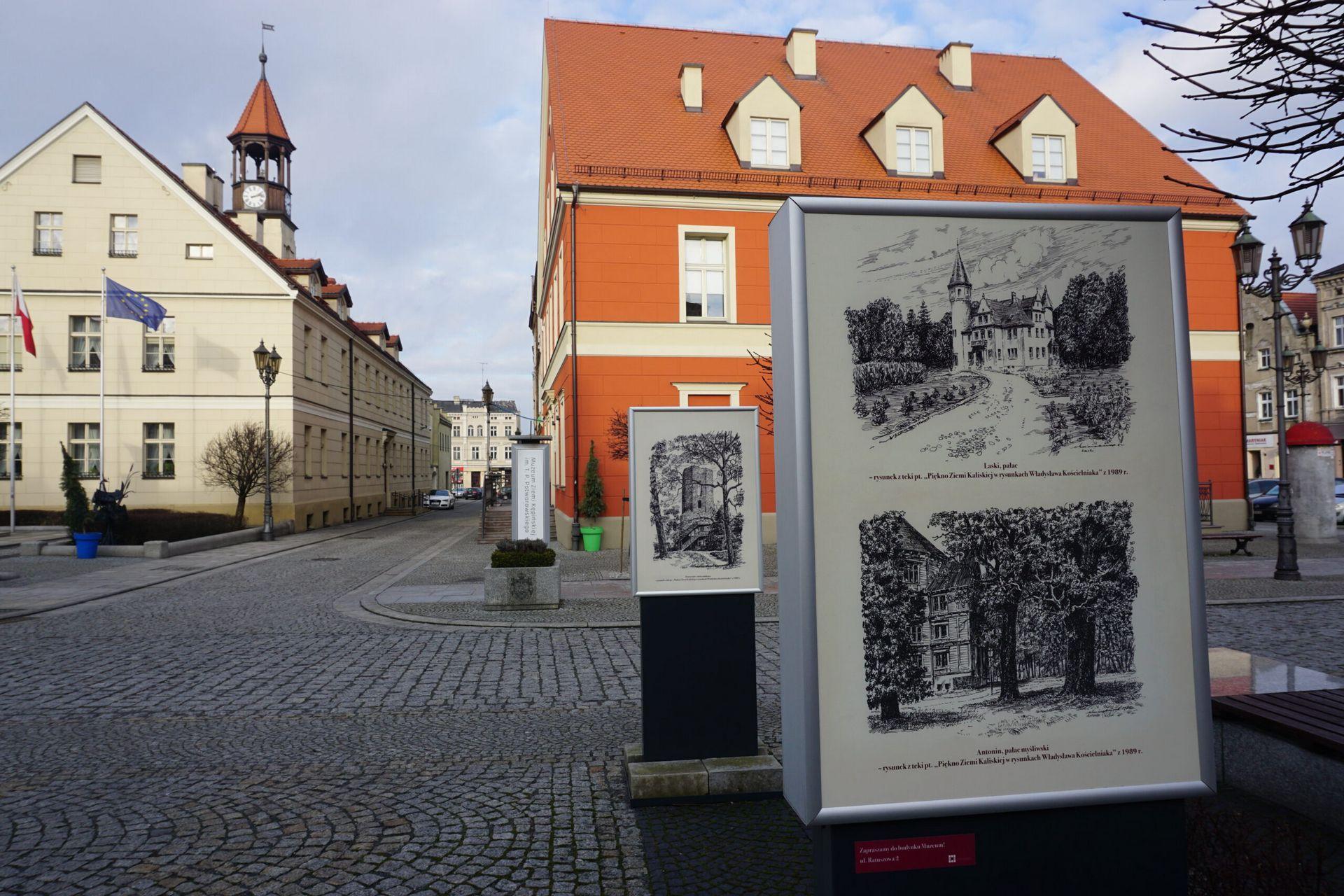 Fotografia jednej z plansz na wystawie plenerowej w tle budynek Muzeum i Ratusz