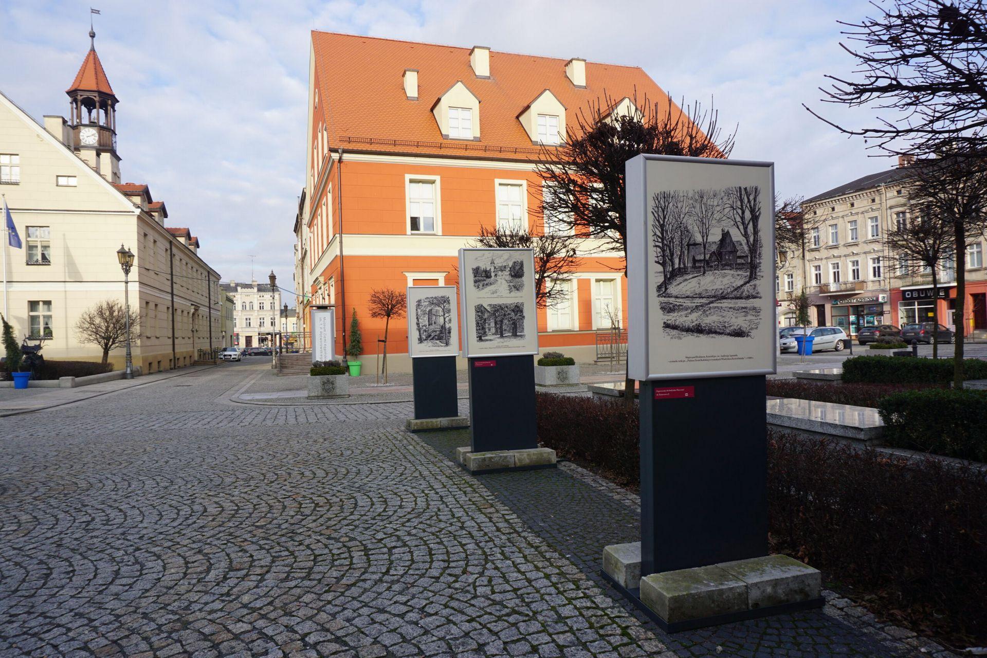 Widok plansz w trzech gablotach w tle budynek Muzeum i Ratusz
