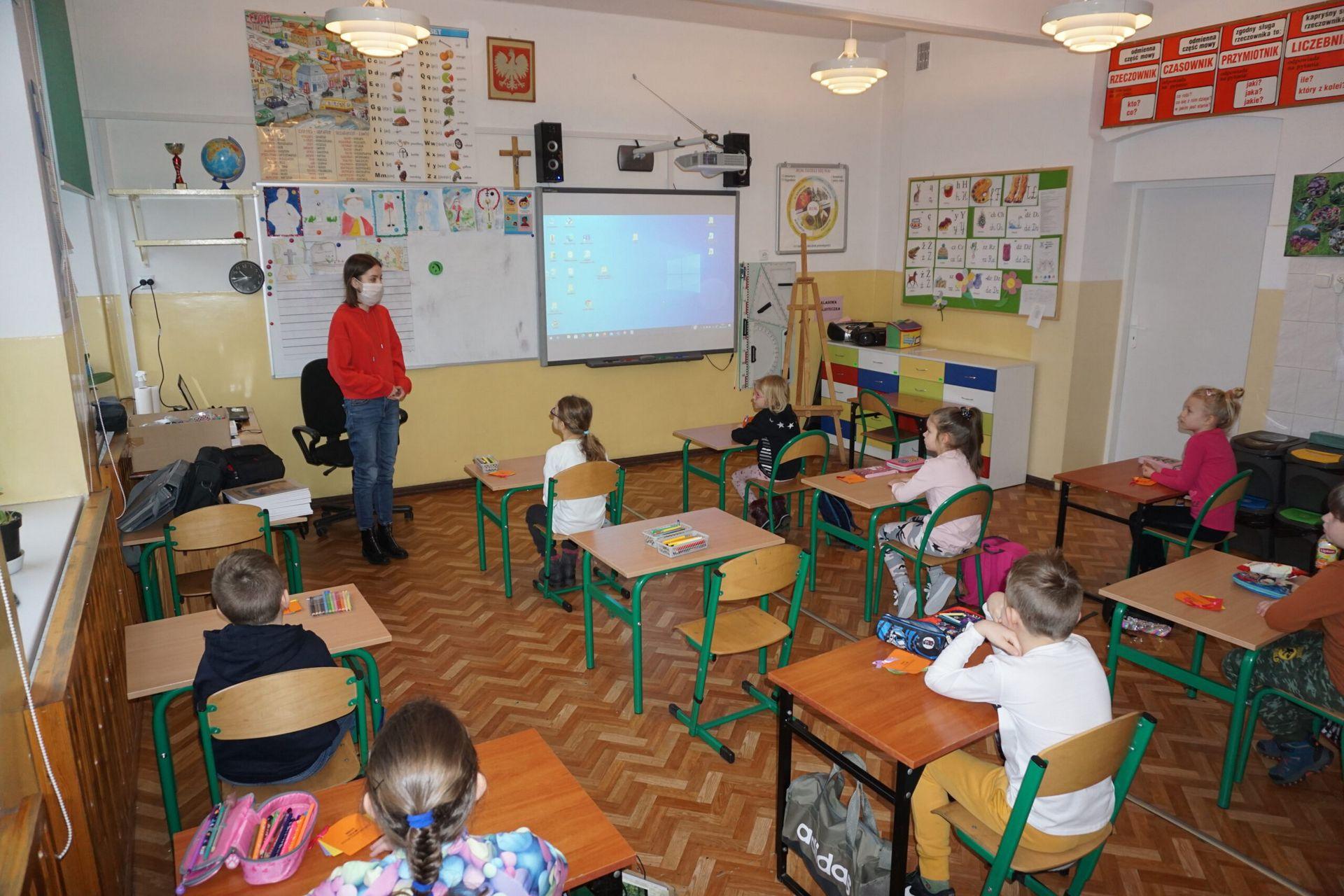 Fotografia warsztatów w sali edukacyjnej dzieci siedzące w ławkach oglądają prezentację na temat malarstwa Potworowskiego