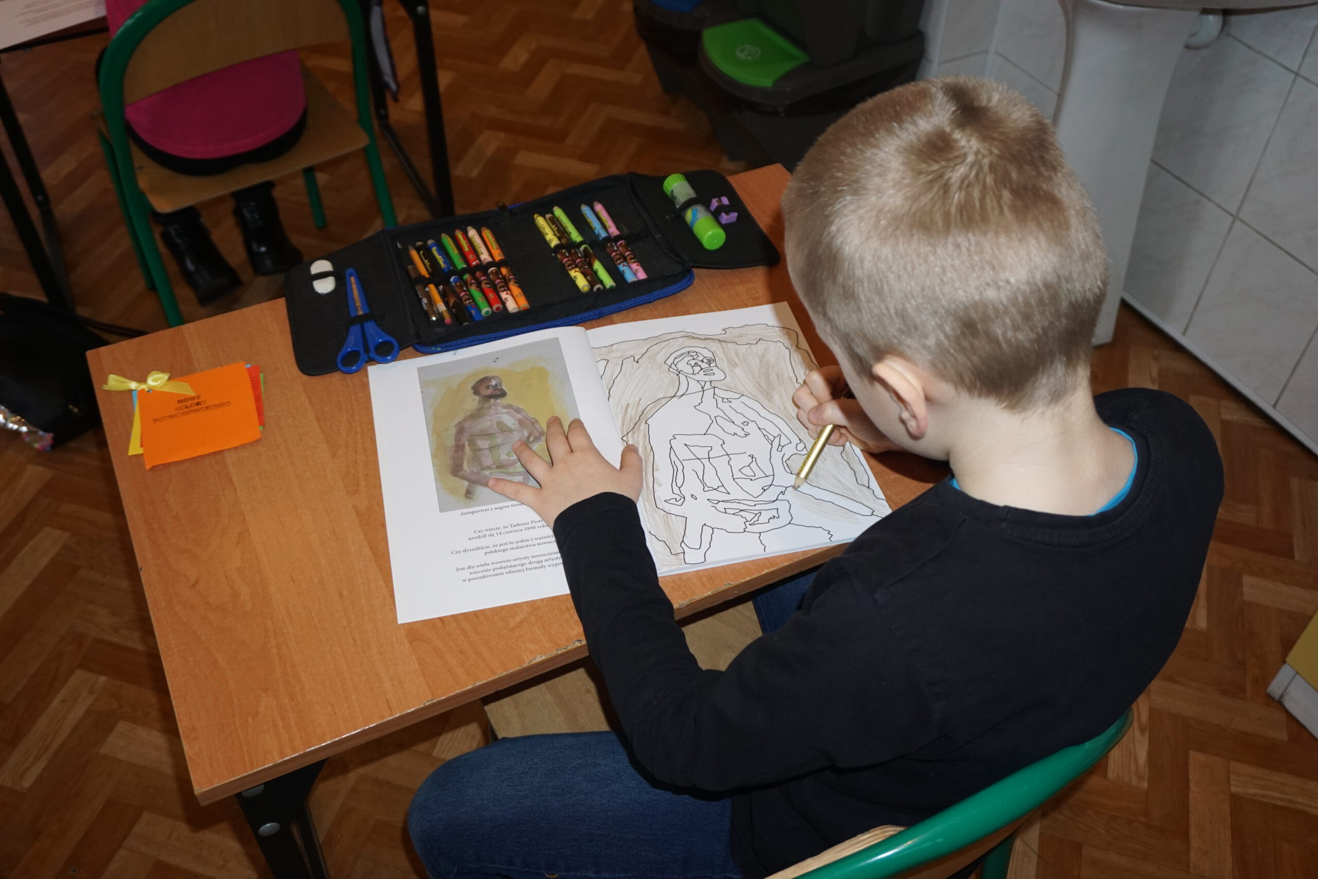 Siedzący chłopiec na krzesełku rysujący obraz malarza Potworowskiego
