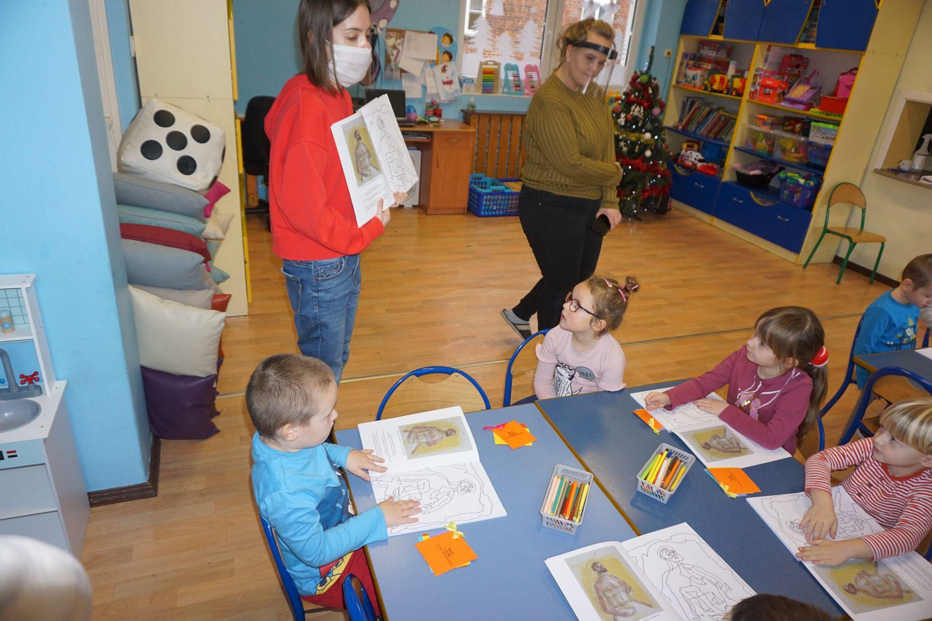 Fotografia dzieci na warsztatach na drugim planie prowadząca zajęcia kobieta i nauczycielka. Dzieci siedzące przy małych stolikach w sali edukacyjnej.