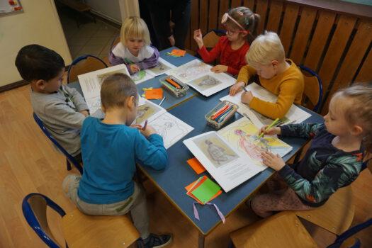 Fotografia 7 dzieci przy stole rysujących na książce o malarzu Potworowskim