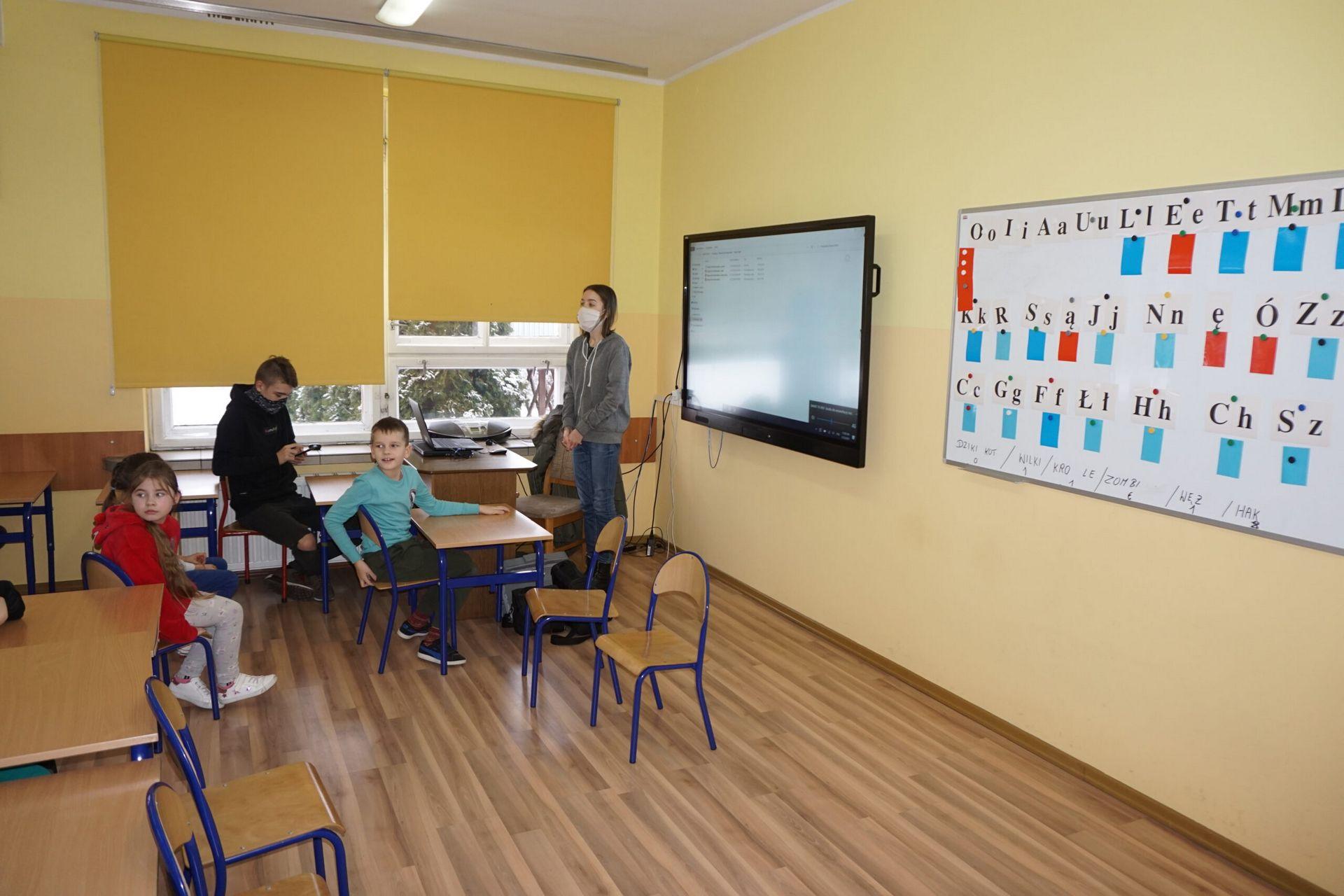 Fotografia warsztatów dzieci siedzące w ławkach i oglądających prezentację