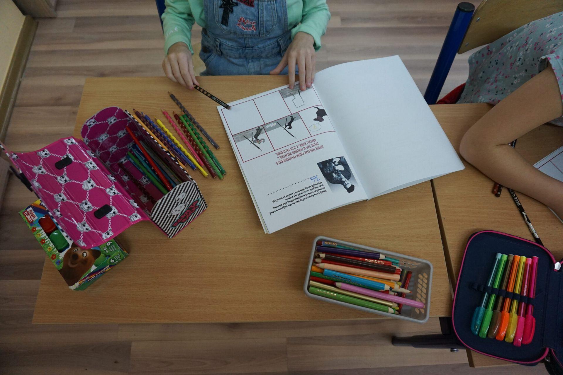 Ręce dziecka na tle kolorowanki przy ławce szkolnej