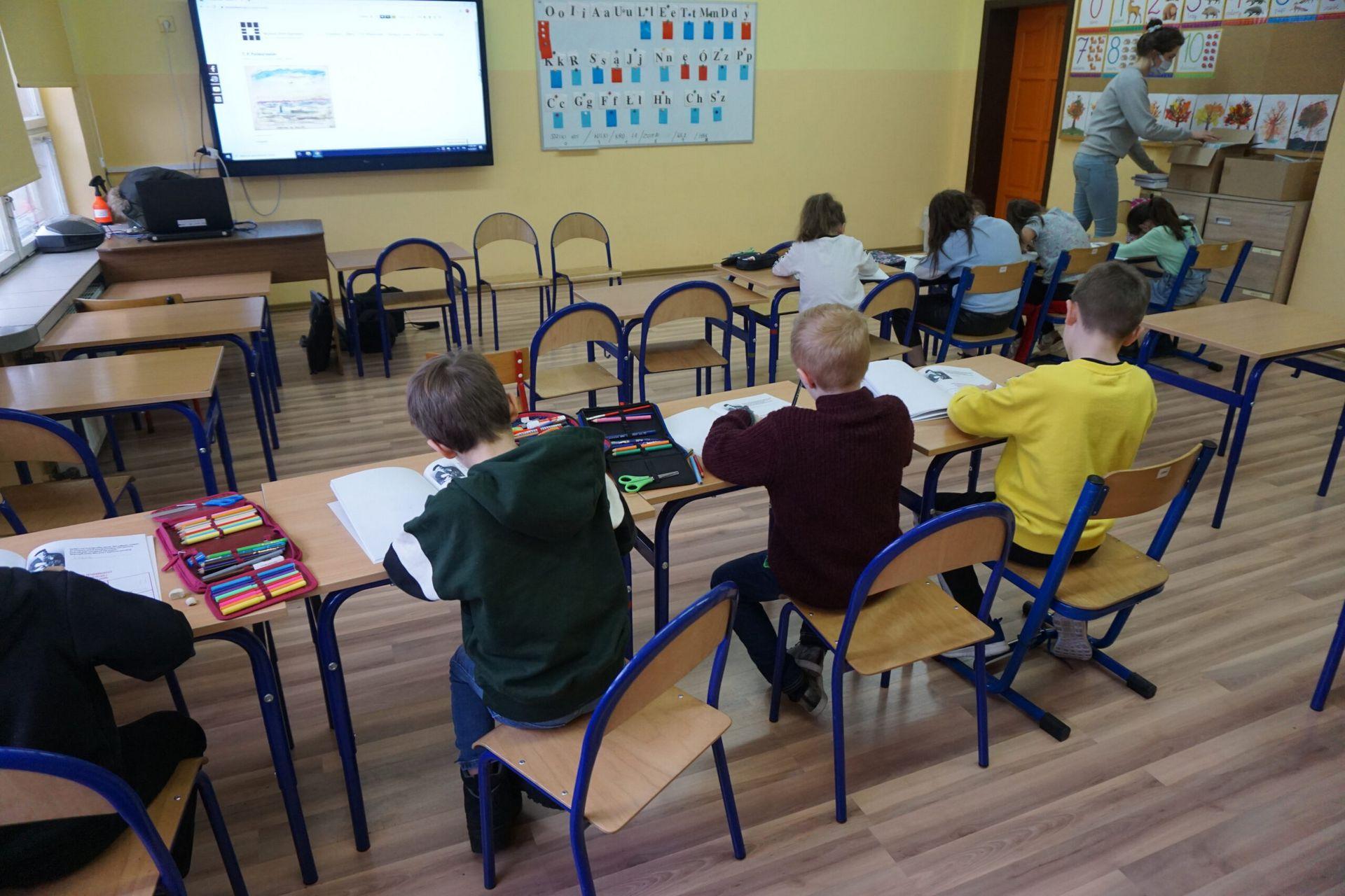 Chłopcy siedzący w ławkach na warsztatach malują rysunki i oglądają prezentację
