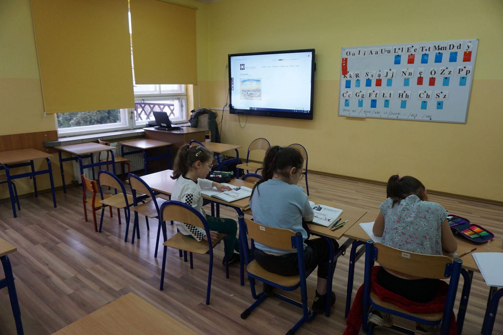 Dzieci siedzące w ławkach na warsztatach