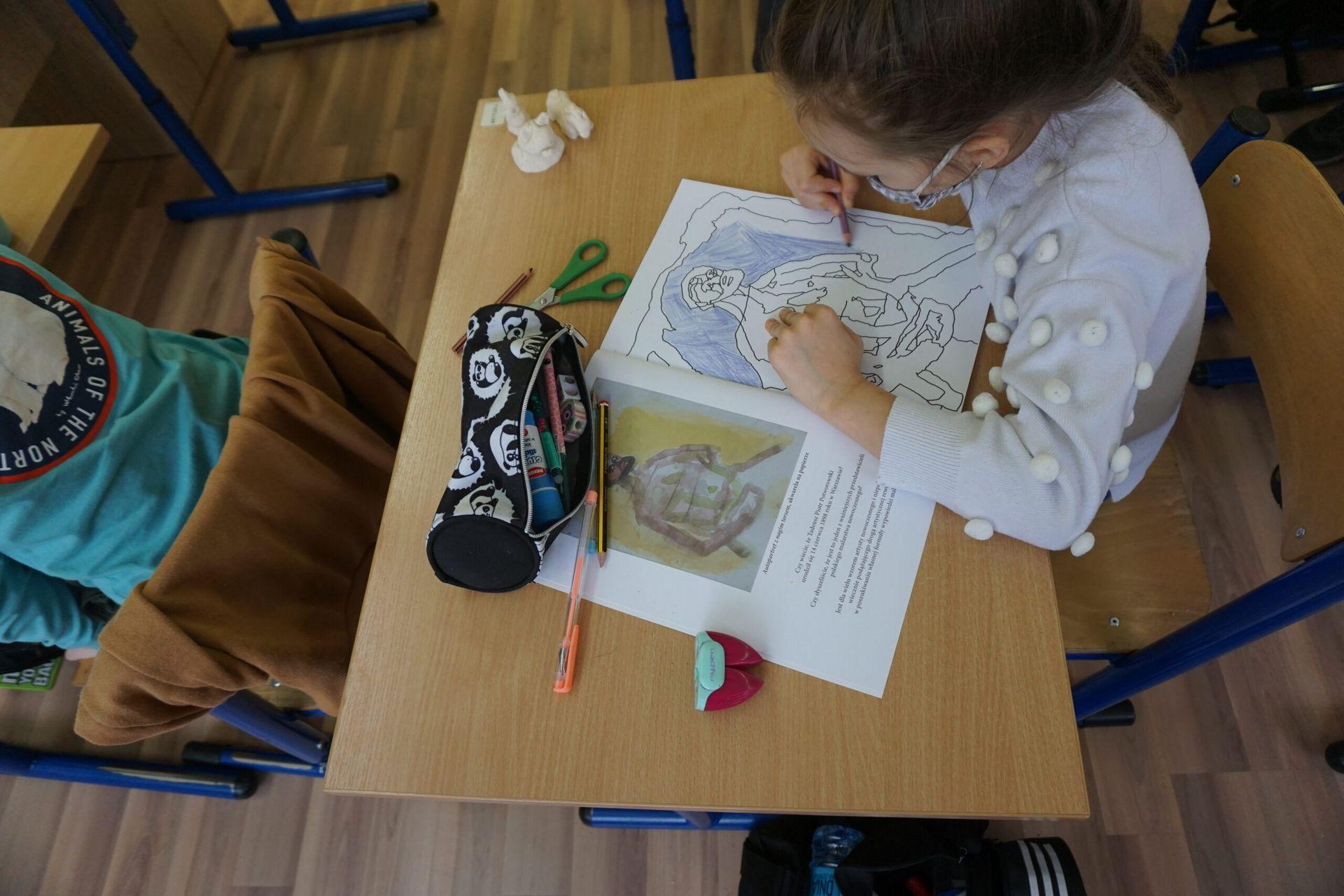 Dziewczynka siedząca w ławce rysująca malunek w kolorowance.