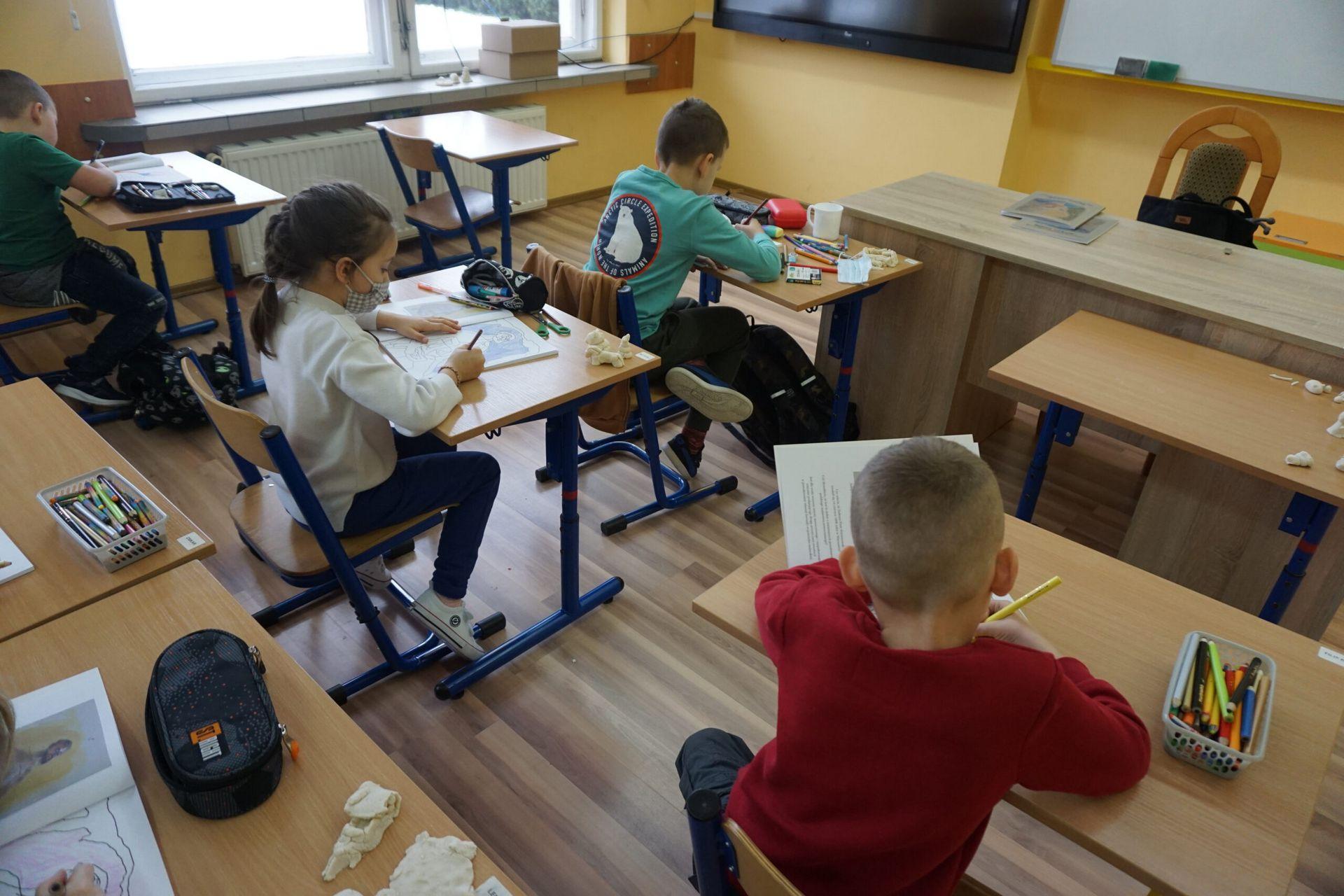 Dzieci siedzące w ławkach szkolnych na warsztatach