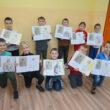 Dzieci prezentujące swoje prace w sali edukacyjnej.