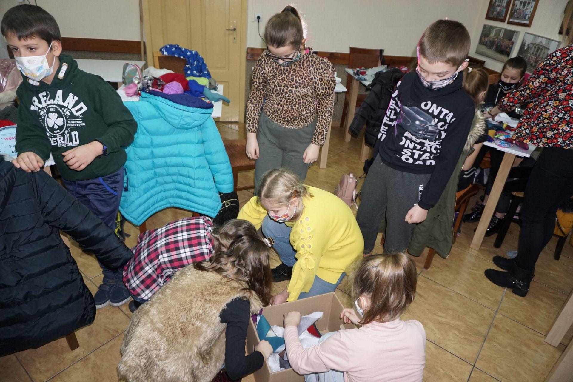 Dzieci stojące i wybierające materiały z różnych tkanin leżące na podłodze