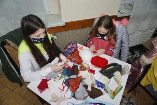 Dwie dziewczynki siedzące przy stole i robiące podczas warsztatów laleczki życzeń