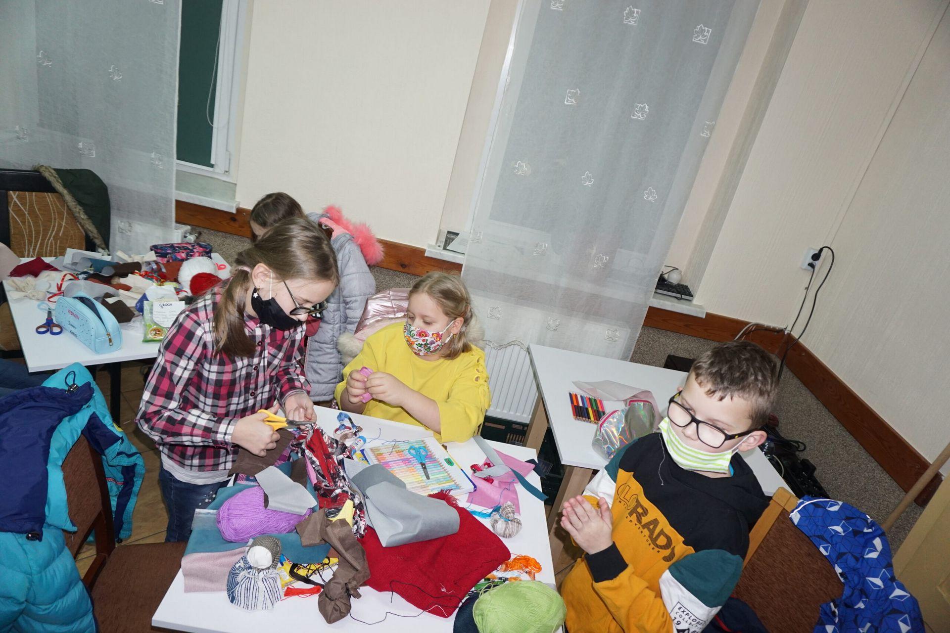 Trójka dzieci siedząca przy stole i wykonujące prace warsztatowe laleczki życzeń