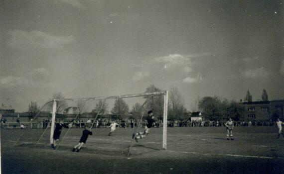 Fotografia boiska piłkarskiego na którym grają piłkarze w oddali drzewa i kibice
