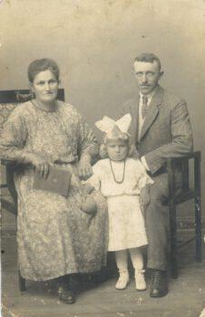 Fotografia kobiety siedzącej po lewej stronie i mężczyzny po prawej stronie oraz pośrodku małej dziewczynki