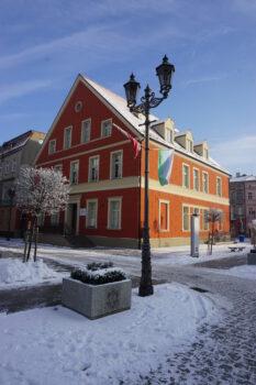 Fotografia budynku muzeum na pierwszym planie latarnia z wiszącymi flagami Polski i Kępna