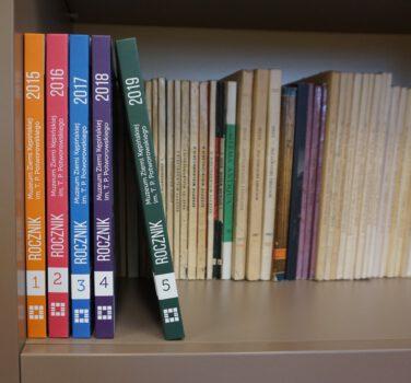 Zdjęcie grzbietów publikacji wszystkich pięciu publikacji Rocznika Muzeum Ziemi Kępińskiej w tle półka z czasopismamy ze zbiorów Muzeum