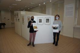 W pomieszczeniu wystawy stałej Muzeum o Potworowskim dwie kobiety trzymające kalendarz na tle obrazów malarza