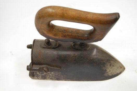 Dawne żelazko z drewnianą rączką.