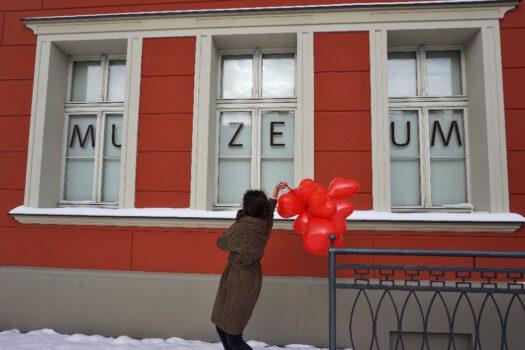 Budynek muzeum trzy okna na szybach napis Muzeum jedna osoba na przodzie trzymająca kilka balanów w kształcie serca