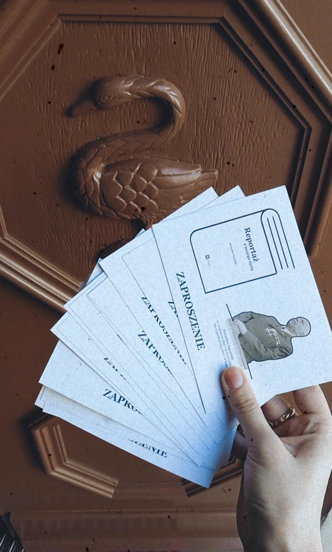 Zdjęcie trzymanych w ręku zaproszeń na wydarzenie promocji publikacji M. Depczyńskiego po prawej stronie fotografia autora po lewej rysunek ksiązki w tle na drzwiach znajduje sięłabędź