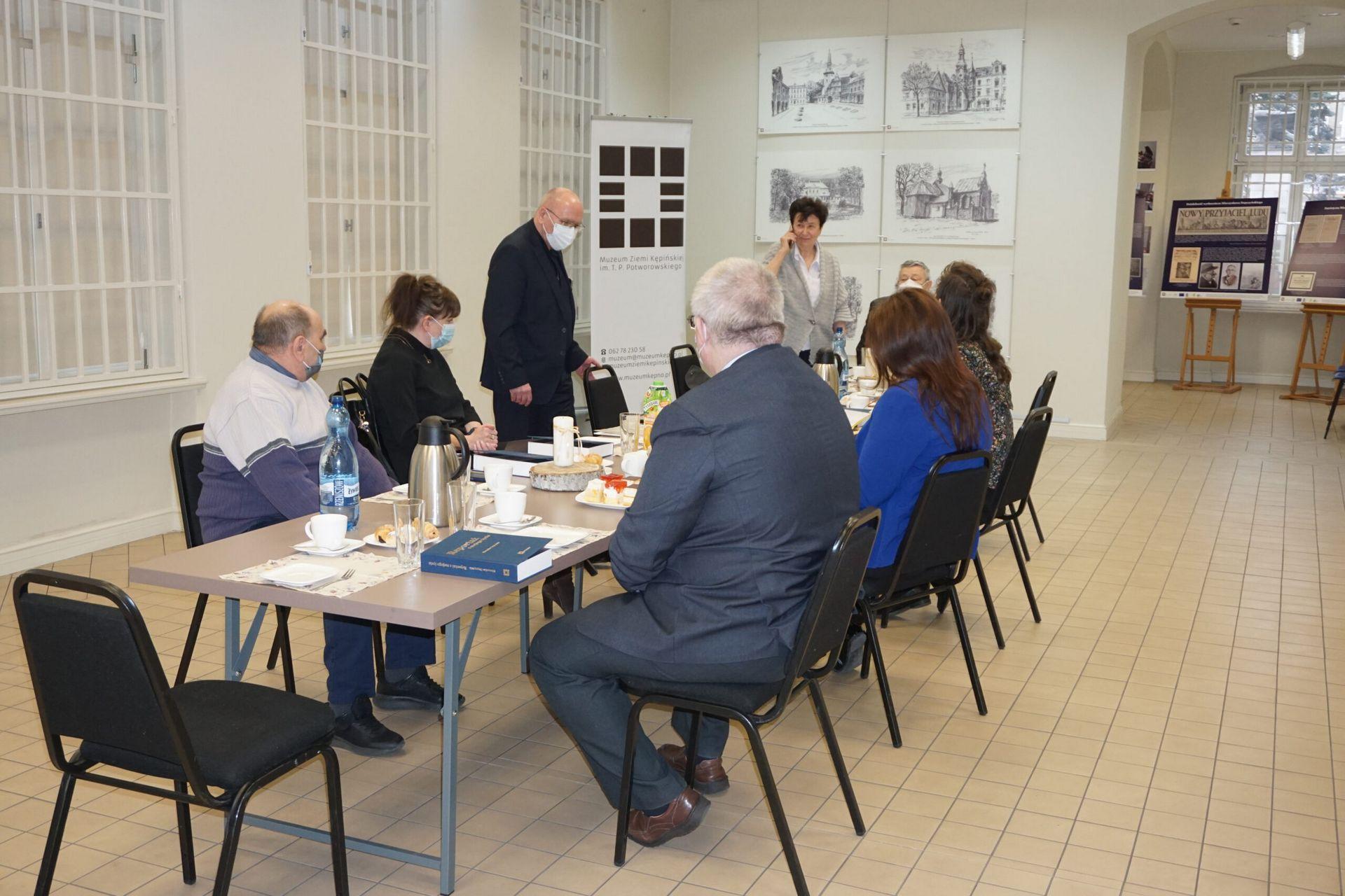 Spotkanie promocyjne publikacji przy stole siedzą zaproszeni goście w sali wystaowej