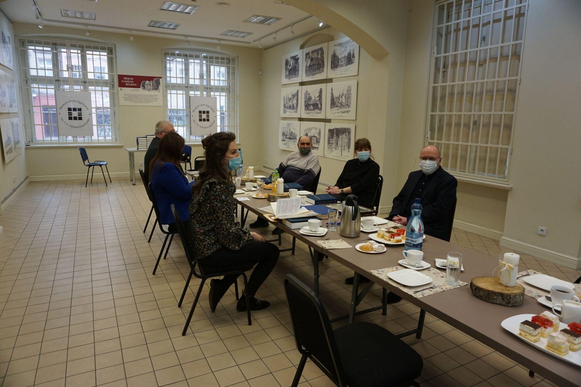 Zdjęcie ze spotkania promocyjnego ksiażżki przy stole siedzi 6 osób