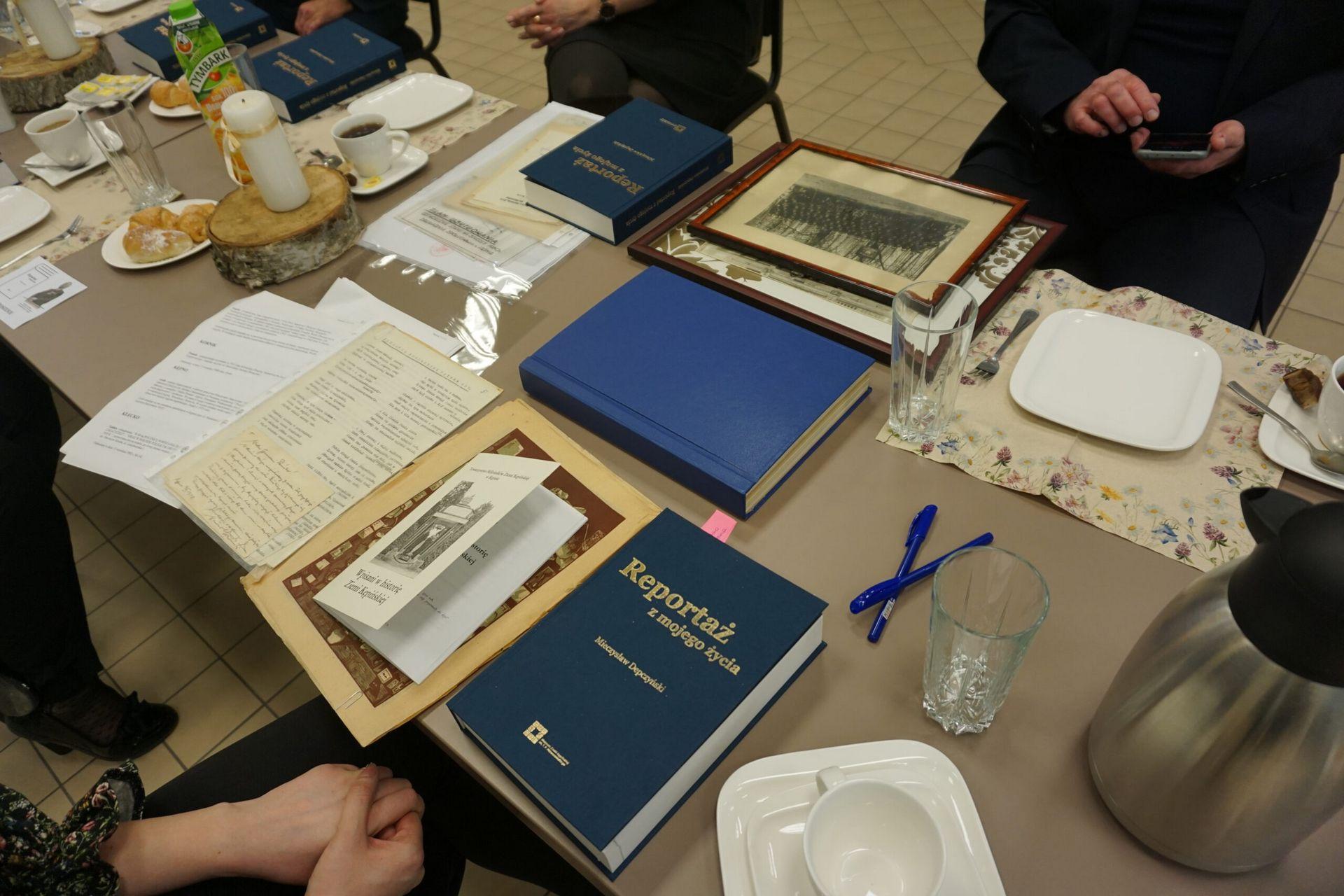 Zdjęcie stołu na którym znajdują się ksiązki i pamiątki związane z Mieczysławem Depczyńskim