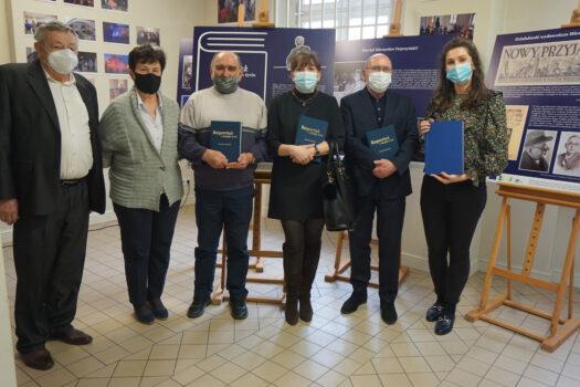 Zdjęcie uczestików spotkanie promocyjnego książki 6 osób stojących przed planszami wystawy czasowej 4 osoby trzymają książki
