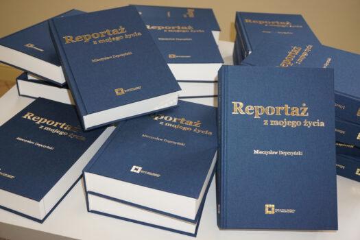 Dużo książek umieszczonych na stole autora Mieczysława Depczyńskiego pt. Reportaż z mojego życia napisy złote okładka granatowa