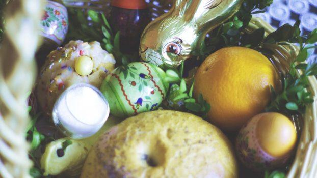 Zdjęcia koszyczka wielkanocne w środku potrawy tradycyjne masło, babeczka, czekolada, sól