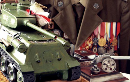 Zdjęcie pamiątek przekazanych przez Mieczysława Pawlika po lewej stronie czołg w tle mudnur z odzznaczeniami