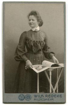 Portret kobiety stojącej i trzymajaca gazetę położoną na małym stoliku