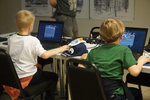 Zdjęcie uczestników warsztatów dwóch chłopców siedzi przed laptopami