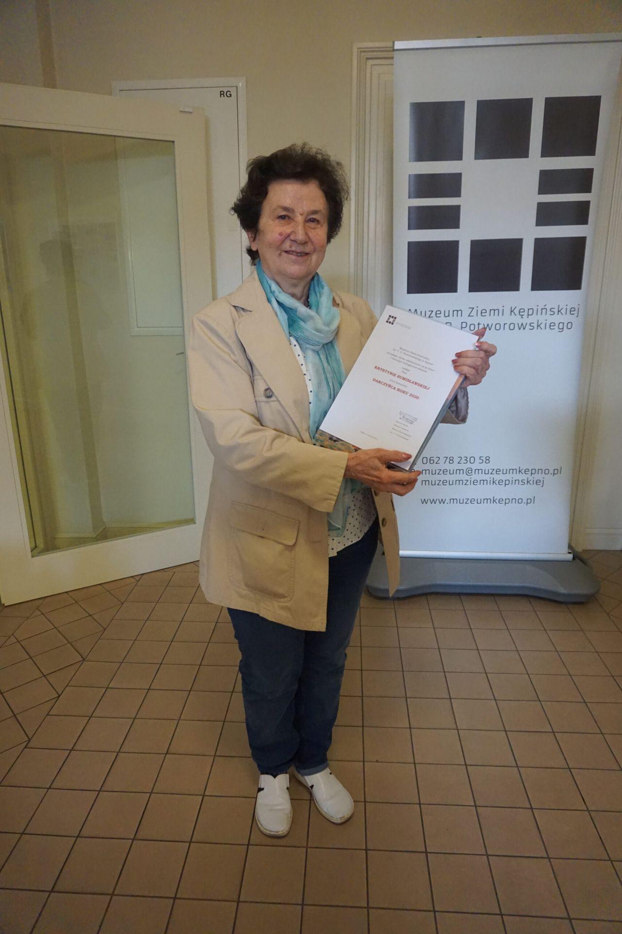 Darczyńca Roku 2020 Pani Krystyna Sumisławska stojąca w korytarzu i trzymająca wyróżnienie