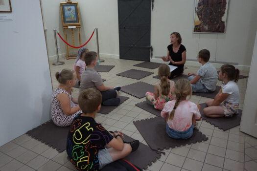 Zdjęcie wykonane podczas warsztatów pastelorelaks dzieci siedzące w wystawie o malarstwie Potworowskiego i prowadząca mówiąca o jego sztuce