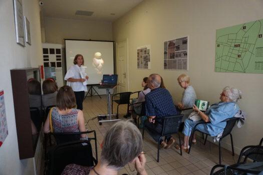 Zdjęcie wykonane na wykładzie o kobietach w sztuce na korytarzu grupa osób siedząca i słuchająca wystąpienia