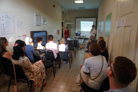 Zdjęcie wykonane podczas werisażu na korytrzu siedzą osoby i wysłuchują wykładu w oddali ekran z wyświetlaną prezentacją
