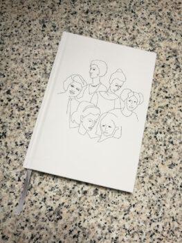 Notes muzealny z grafikami twarzy kobiet