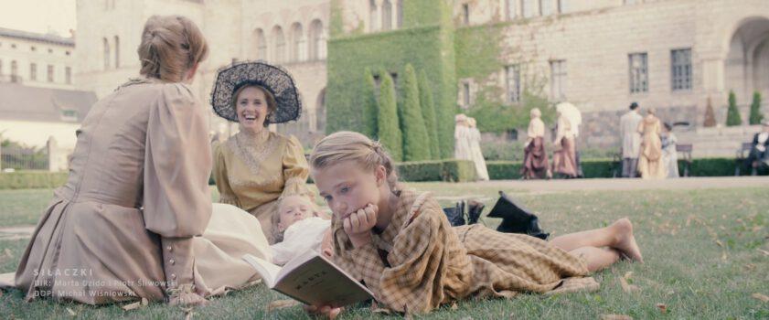 Silaczki_5 fot. Michal Wisniowski kobiety leżące na trawie jedna z nich czyta książkę w oddali budynek i zielony bluszcz na budynku