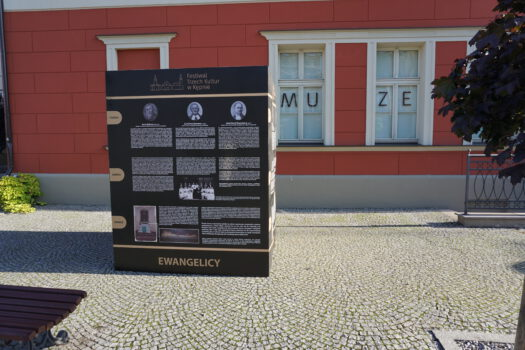 Wystawa plenerowa pt. Wielokulturowość w trzech słowach przed budynkiem muzeum czarne plansze i zdjęcia różnych postaci związanych z daną religią