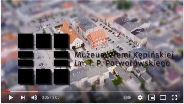 Zdjęcie z filmu logo muzeum kwartart prezentujące rynek oraz w tle widok z lotu ptaka centrum miasta