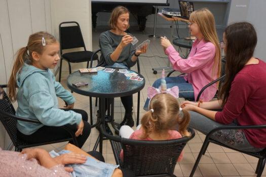 Grupa osób siedząca przy stoliku i grająca w grę piotruś