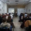Wykład artystki feministki w sali obrazów T. P. Potworowskiego na zdjęciu grupa ludzi siedząca słuchająca prezentacji
