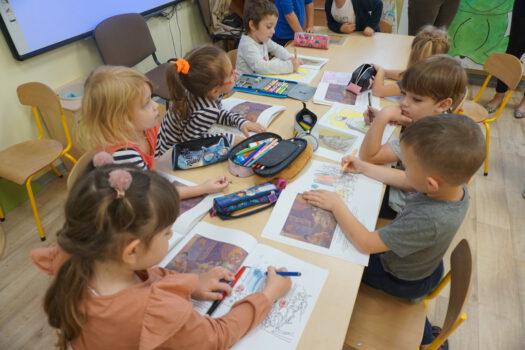 Przedszkolaki wykonują prace plastyczne przy stoliku